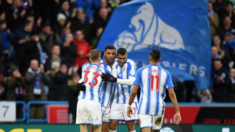 Steve Mounie is mobbed by his Huddersfield Town team-mates after scoring