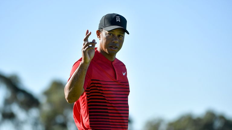 Tiger Woods motions to the crowd after a putt on the 14th at the Farmers Insurance Open