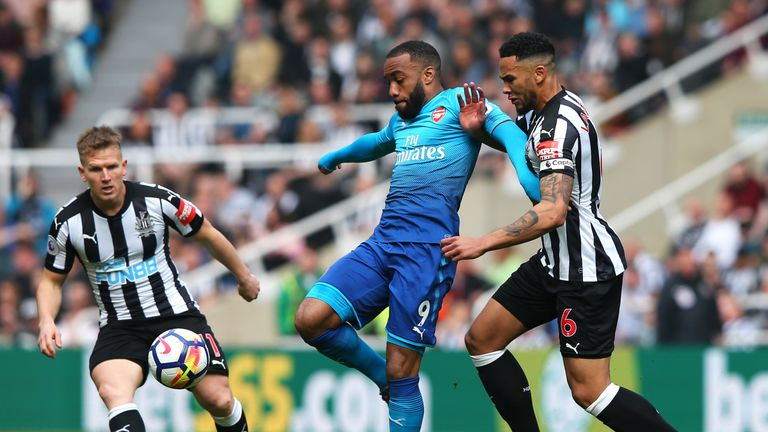 Arsenal's Alexandre Lacazette battles for the ball with Newcastle defender Jamaal Lascelles
