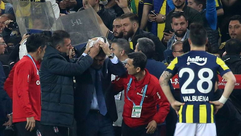 Besiktas head coach Senol Gunes holds his head after being hit by an object during the abandoned Turkish Cup semi final