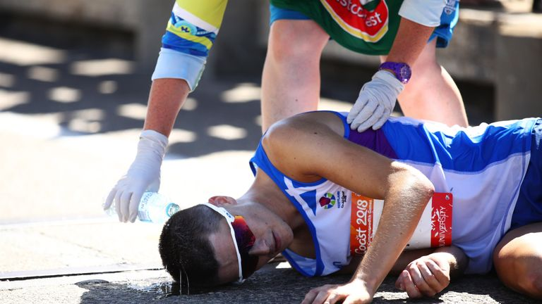 Callum Hawkins is given assistance after collapsing in the men's marathon