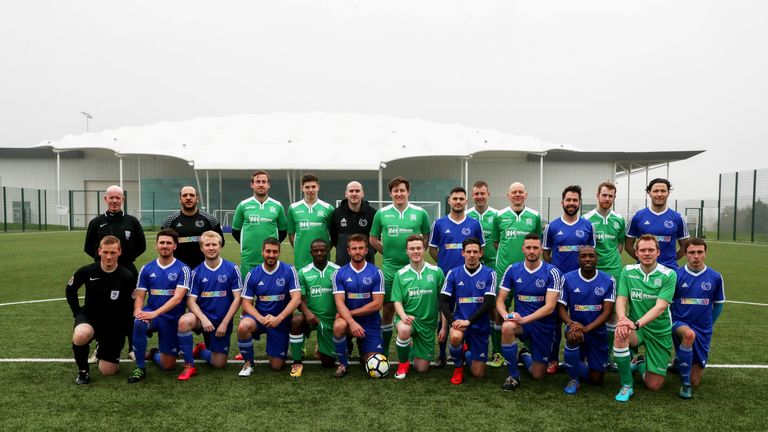 Players from Stonewall FC and UKPFC, and referee Dermot Gallagher and his assistants, pose for a photo