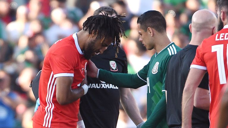 Ashley Williams is consoled by Javier Hernandez after suffering  rib injury against Mexico