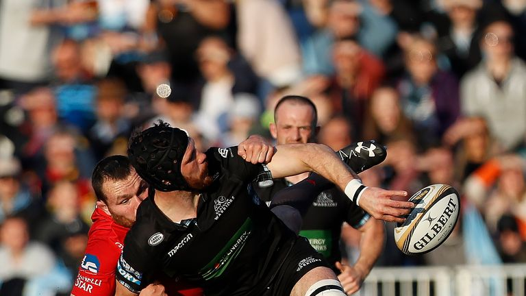 Tim Swinson of Glasgow Warriors is tackled by Rob Evans of Scarlets