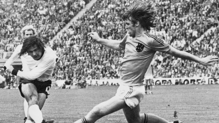 West German forward Gerd Muller (L) scores the second goal for his team despite the being pressured by Dutch defender Rudi Krol during the World Cup final