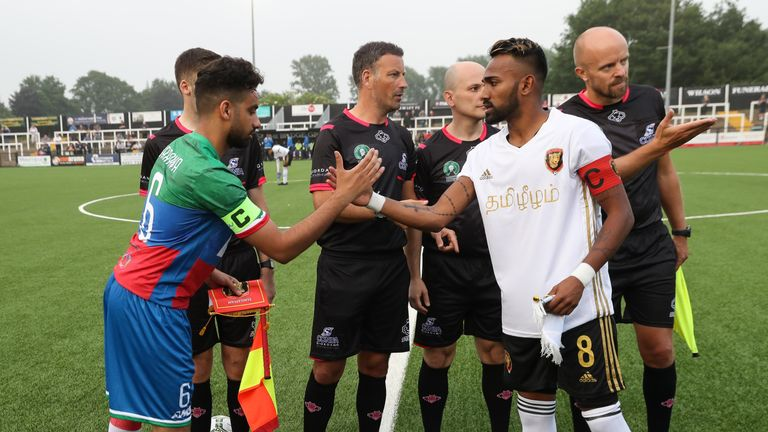 The captains of Barawa and Tamil Eelam shake hands before kick-off at Bromley, watched by referee Mark Clattenburg