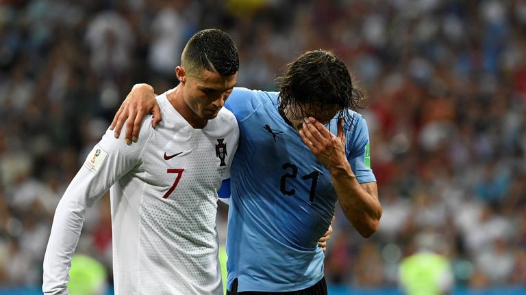Cristiano Ronaldo helps an injured Edinson Cavani from the field