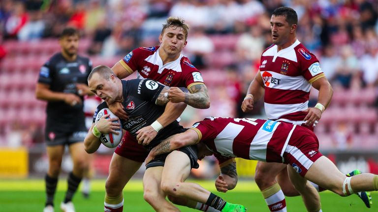 St Helens' Adam Swift is tackled by Wigan's Sam Powell and John Bateman