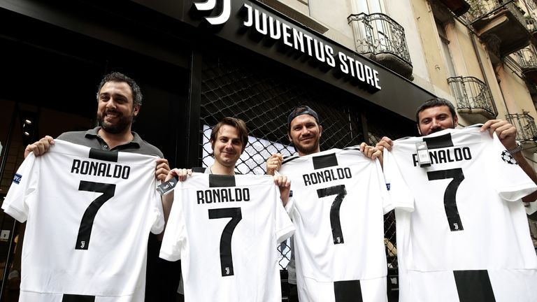 Juventus supporters pose with a Cristiano Ronaldo No 7 shirt in front of the Juventus store