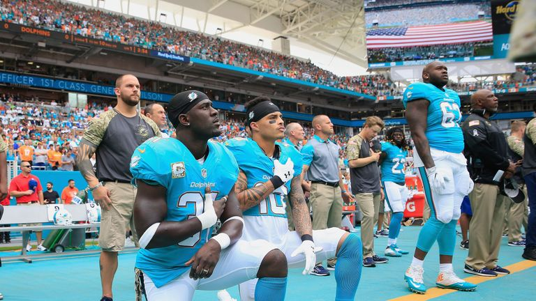 Michael Thomas #31  and Kenny Stills #10 of the Miami Dolphins take a knee during the national anthem