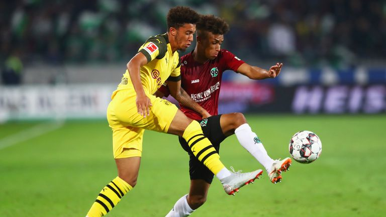 Dortmund's Jadon Sancho (L) and Hannover's Linton Maina battle for possession