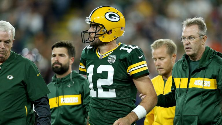 Aaron Rodgers leaves the field to have his knee assessed against Chicago