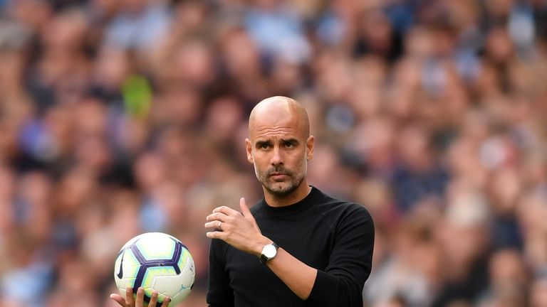 Manchester City boss Pep Guardiola holding ball on the touchline