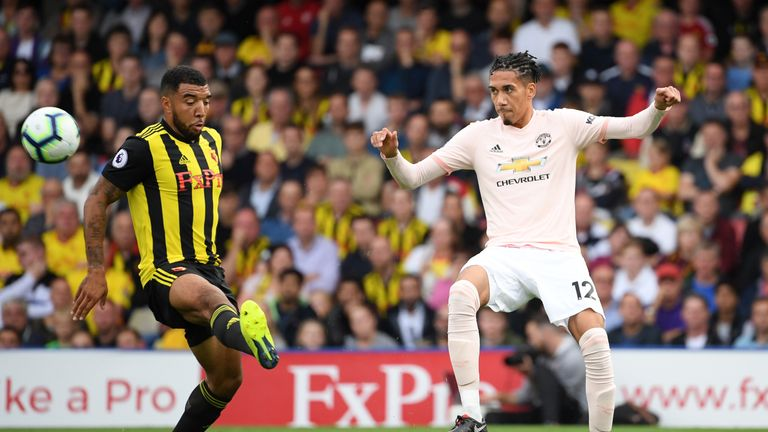 Troy Deeney and Chris Smalling battle for the ball at Vicarage Road