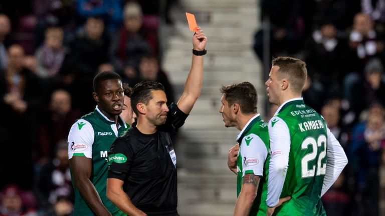 Referee Andrew Dallas shows a red card to Hibernian's Florain Kamberi