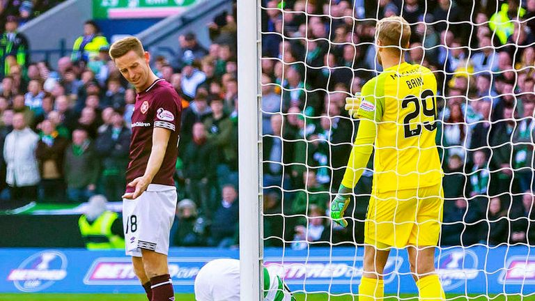 Steven Maclean looks on as Celtic's Eboue Kouassi lays on the ground