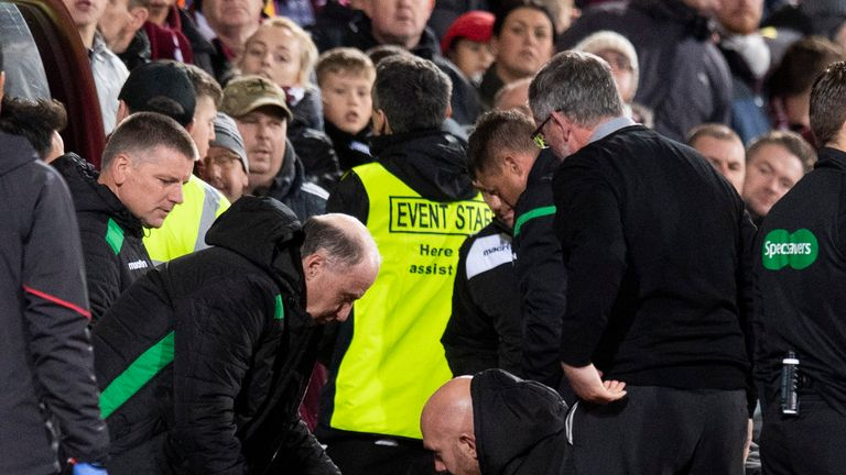 Hibernian manager Neil Lennon is helped to his feet after appearing to be struct by an object from the crowd