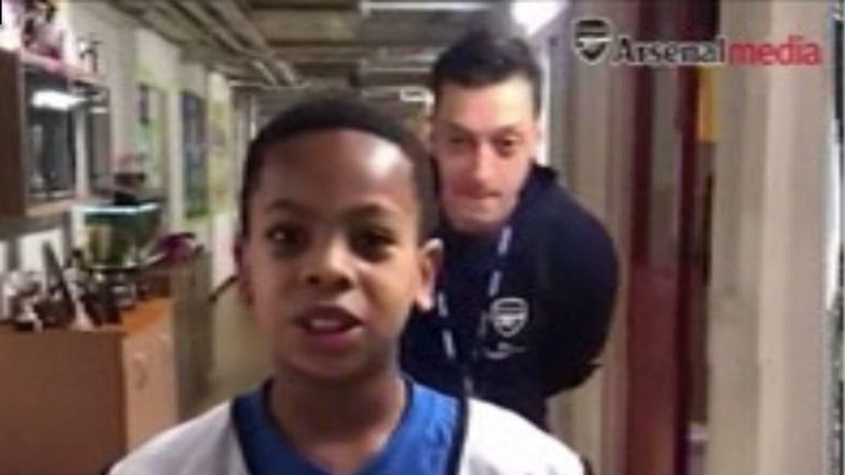 Mesut Ozil surprises a young Arsenal fan at a London primary school.