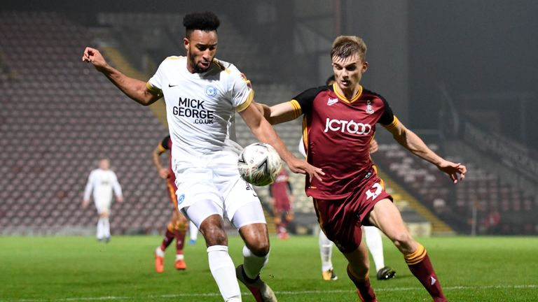 Peterborough's Rhys Bennett (L) competes with Bradford's George Miller