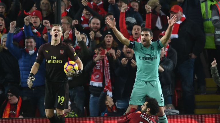 Arsenal players protest as referee Michael Oliver awards Liverpool a penalty at Anfield