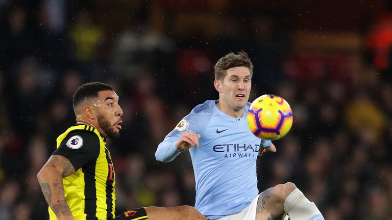 Troy Deeney and John Stones in action at Vicarage Road