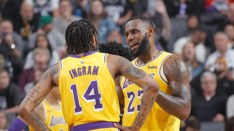 LeBron James talks to team-mate Brandon Ingram on court