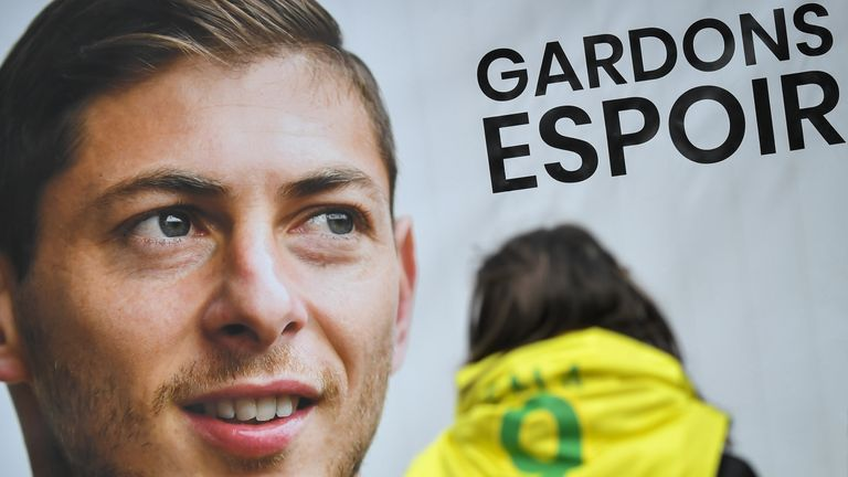 A Nantes supporter stands beside a portrait of Emiliano Sala outside the club's training centre
