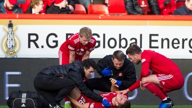 Aberdeen's Tommie Hoban was treated for a knee injury on the pitch at Pittodrie