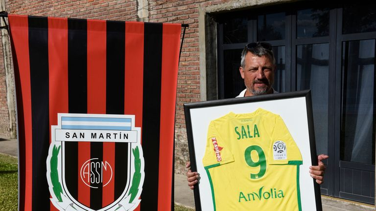 Daniel Ribero, President of San Martin Club, poses with Sala's framed jersey at the club where the wake took place