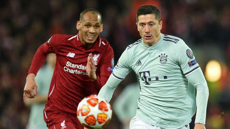 Fabinho and Robert Lewandowski tussle for the ball at Anfield