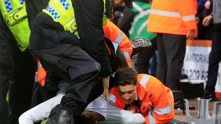 A Newcastle United fan is removed from the pitch by stewards and police