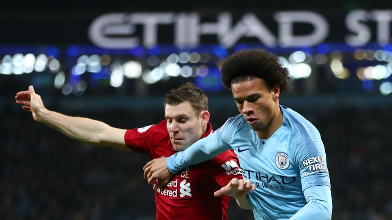 Manchester City winger Leroy Sane tussles with Liverpool's James Milner