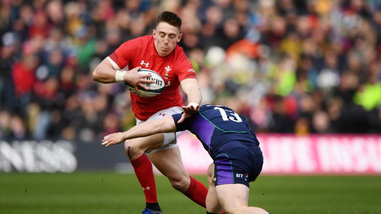 Josh Adams  is tackled by Nick Grigg  during Wales' win over Scotland