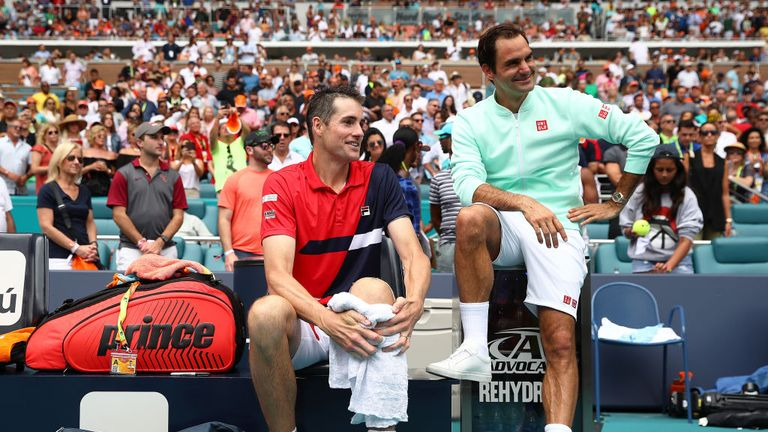Federer sits with an injured Isner as they watch tournament director James Blake make his introductory speech