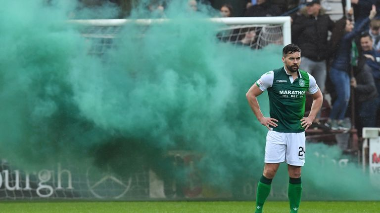 Hibernian's Darren McGregor looks on as a smoke bomb is let off behind him