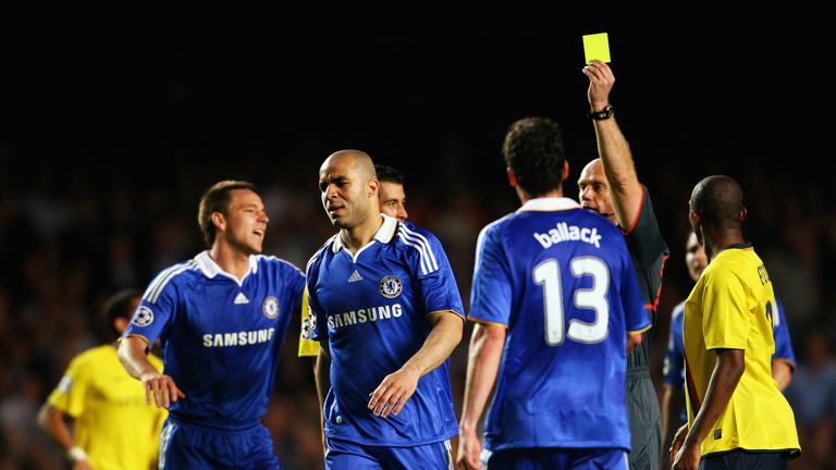 Chelsea defender Alex is shown a yellow card during a bad-tempered match