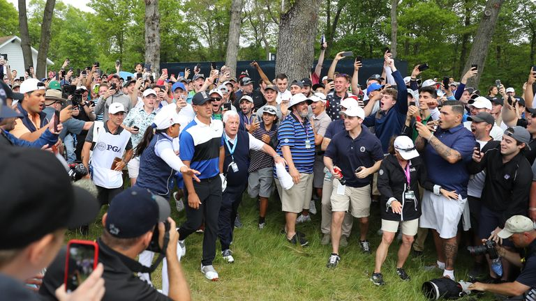 Koepka braves the New York fans after playing a shot from the rough