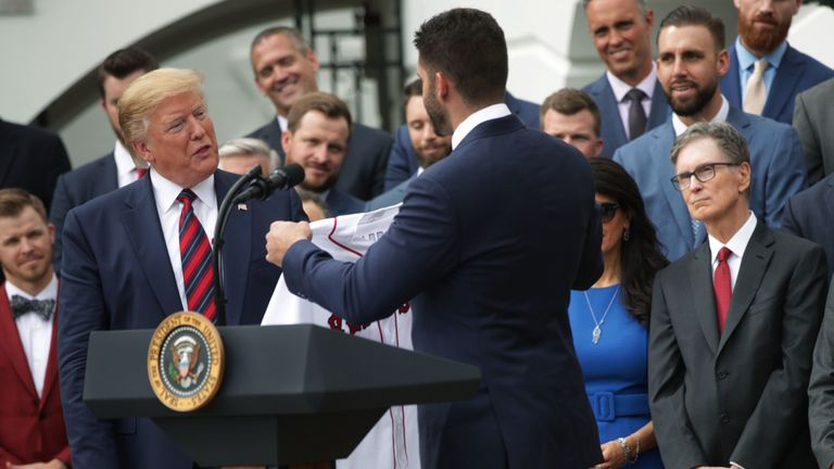 President Trump is presented with a jersey by J.D. Martinez of the Boston Red Sox in 2018 as principal owner John W Henry looks on