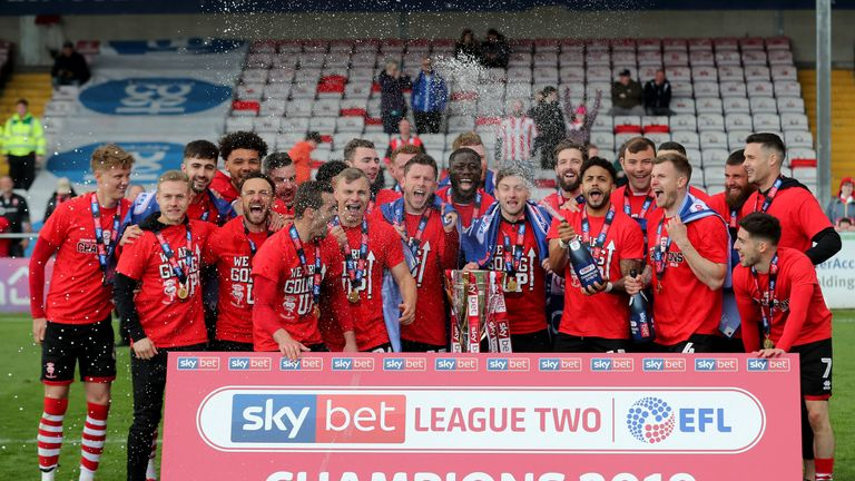 Lincoln City's players celebrate with the League Two trophy
