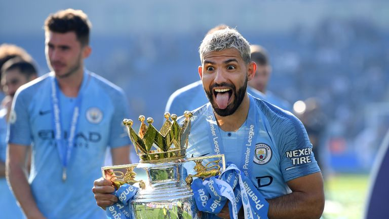 Aguero celebrates with the Premier League trophy - one of three trophies he won at City this season