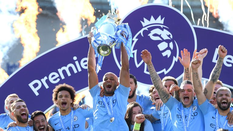 Vincent Kompany lifts the Premier League trophy after Manchester City are crowned back-to-back champions