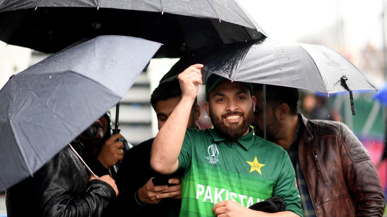 Pakistan fans shelter under their umbrellas at the abandoned World Cup tie against Sri Lanka at Bristol