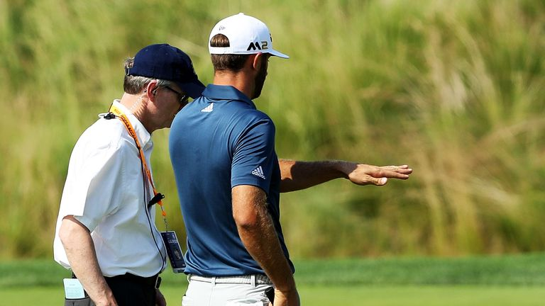 Dustin Johnson chats with a rules official on the fifth green during the final round in 2016