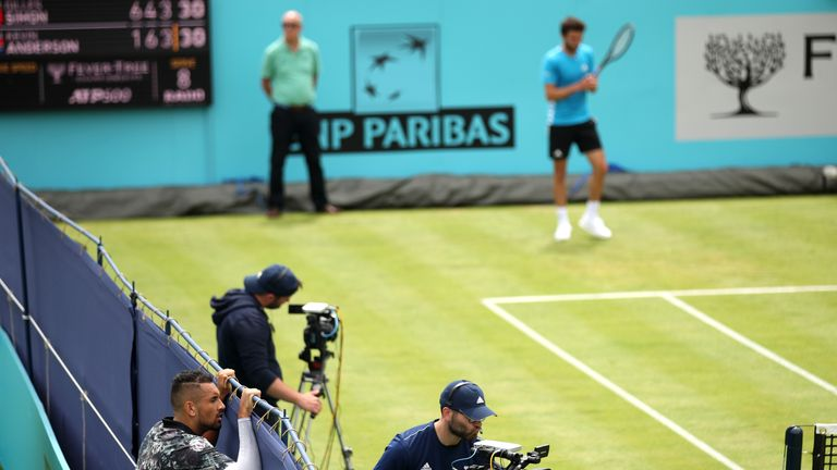 Kyrgios peers over a fence to watch the game on court one