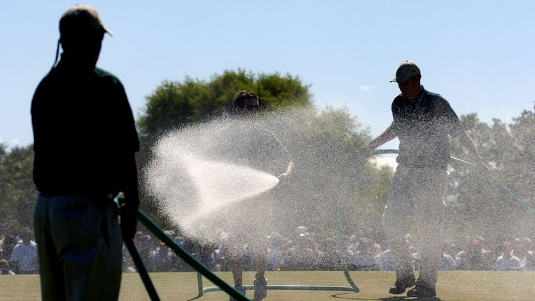 Ground staff water the greens between groups on the final day in 2004