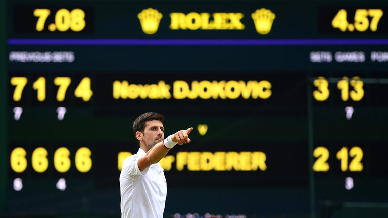 Djokovic celebrates with the electronic scoreboard in the background