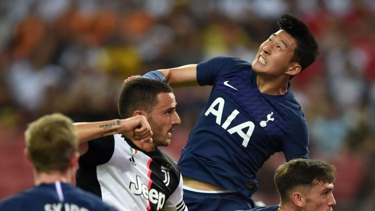 Tottenham Hotspur's Son Heung-Min jumps to head the ball past Juventus' Leonardo Bonucci (left)