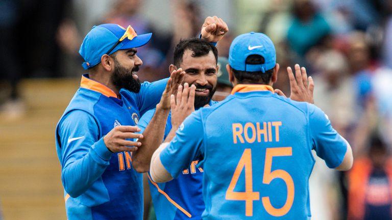Virat Kohli of India (L) congratulates  Mohammed Shami (centre) on taking the wicket of Tamim Iqbal of Bangladesh