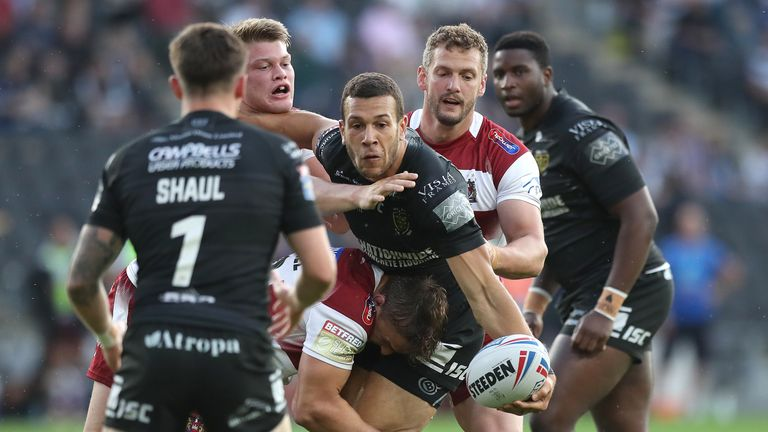 Hull FC's Carlos Tuimavave is tackled by Wigan Warriors Morgan Smithies (l), Sam Powell and Sean O'Loughlin (r)