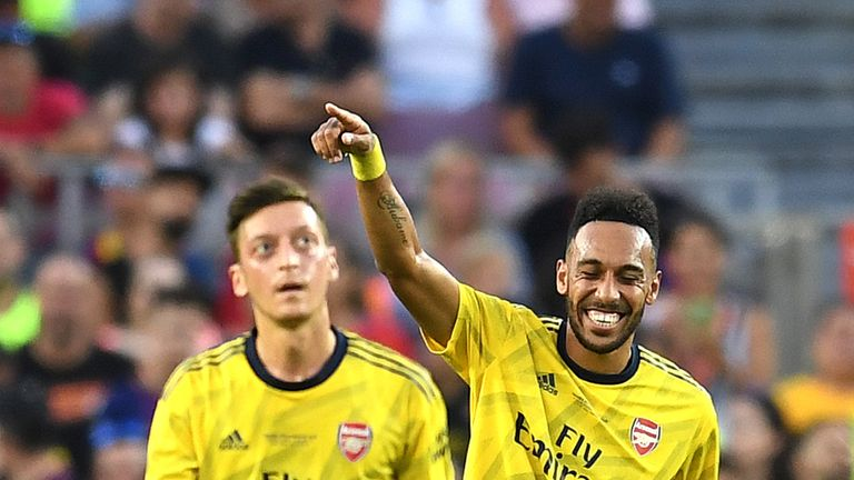 Pierre-Emerick Aubameyang celebrates with Arsenal team-mate Mesut Ozil after scoring against Barcelona